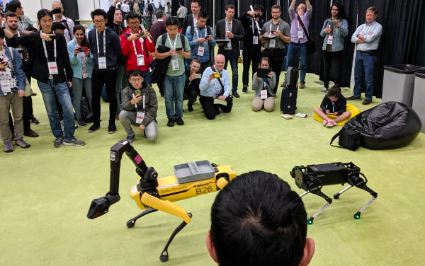 Boston Dynamics quadruped robot with arm and another quadruped.