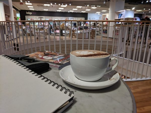 A notebook in a bookstore coffeehouse, with coffe.